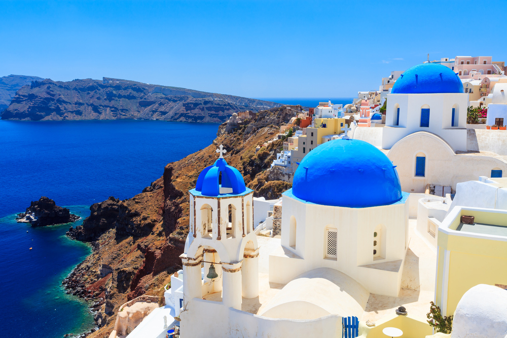Santorini, Greece, panoramic white buildings against blue sea and sky.